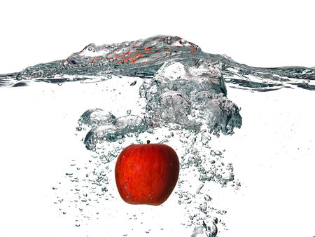 Closeup of red apple falling into fresh water isolated on white background photo