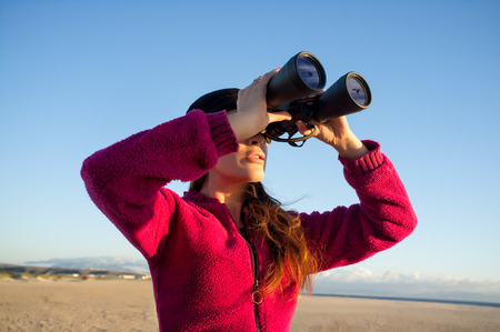 Ecologist young woman watching the environment birds on the coast with binoculars. Wide angle of view photo