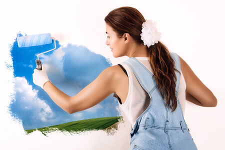 ecologist: Young woman painting a nature landscape on wall with roller. Mural painting on wall. Ecologist