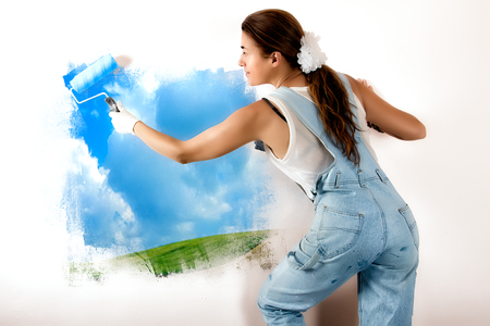 Young woman painting a nature landscape on wall with roller. Mural painting on wall. Ecologist photo