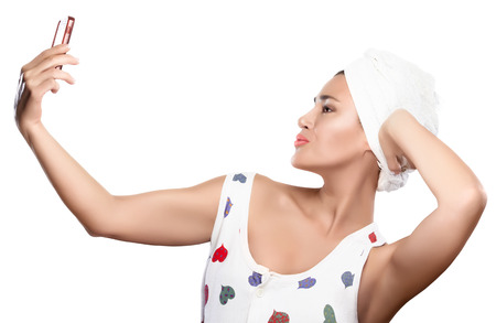 Young woman with towel on head makes selfie sending a kiss with her mobile phone  Self Portrait with smart phone photo