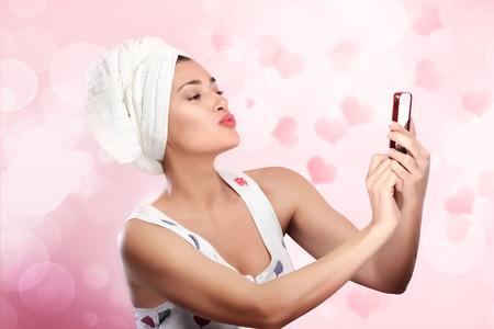 mujer bañandose: Mujer joven con la toalla en la cabeza hace selfie envía un beso con su teléfono móvil Autorretrato con el teléfono inteligente Foto de archivo