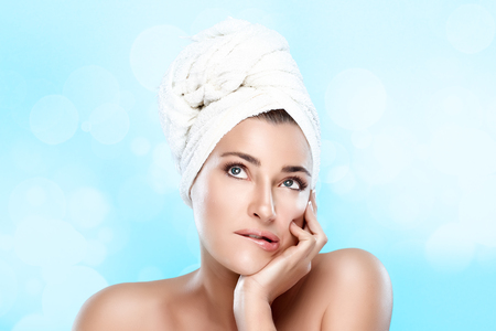 Spa woman with towel on head thinking looking up. Haircare and bodycare concept photo