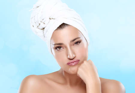 bodycare: Young worried woman with towel on head pouts looking at camera. Closeup portrait. Haircare and bodycare Stock Photo