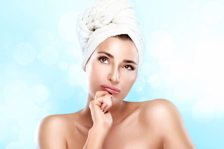Spa woman with towel on head thinking looking up. Haircare and bodycare concept. Closeup portrait photo