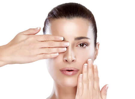 Beautiful spa woman with hands on her face covering one eye. Perfect skin. Skincare concept. Nude makeup. Portrait isolated on white