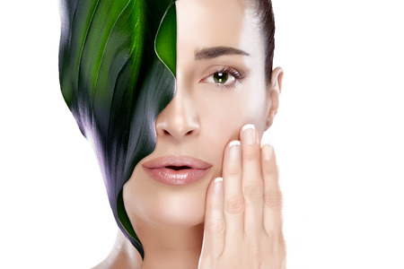 Beautiful spa woman with leaf on her face covering one eye. Perfect skin. Skincare concept. Portrait isolated on white