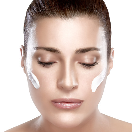 woman face cream: Beautiful spa woman looking down with cream on her face. Perfect skin. Spa treatment. Skincare concept.  Portrait isolated on white.