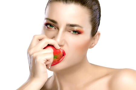 Beautiful young woman with red and green makeup biting an apple. Closeup portrait isolated on white background photo