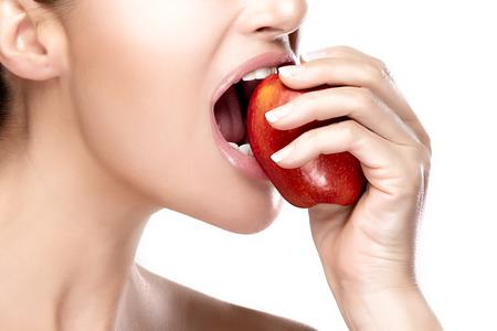 boca sana: Detalle de la hermosa y saludable la boca mordiendo una manzana roja. Retrato del primer aislado en el fondo blanco
