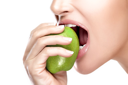Closeup of beautiful healthy mouth biting a juicy and acid green apple. Closeup portrait isolated on white background