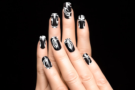 Closeup of woman hands with art nail design. Fashion print nail stickers. Manicure and Nail tattoo photo