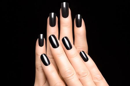 黒の爪を女性の手のクローズ アップ。マニキュア 写真素材
