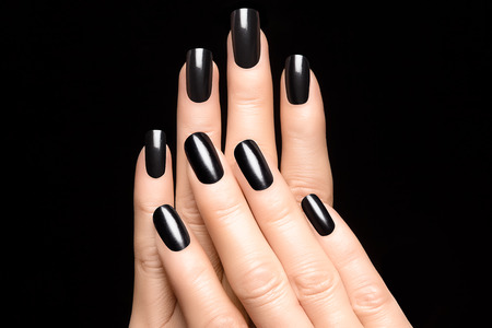 sparkles: Closeup of woman hands with black nails. Manicure Stock Photo