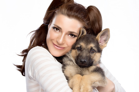 endearment: Beautiful girl tenderly hugging a German Shepherd puppy. Cute young woman with a puppy dog. Portrait isolated on white