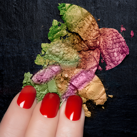 Closeup of fingers with red nails and colorful crushed eye shadow on black stone. Manicure and makeup concept photo