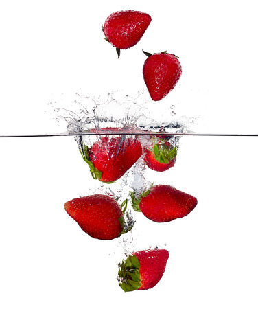 Closeup of fresh and health strawberries falling into clear water isolated on white background. Washing fruit Zdjęcie Seryjne