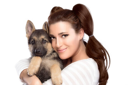 Beautiful girl tenderly hugging a German Shepherd puppy. Cute young woman with a puppy dog. Portrait isolated on white photo