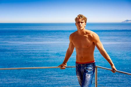 Vacaciones ideales. Hombre joven rubio hermoso en pantalones vaqueros y tomar el sol sin camisa en el balcón con el mar de fondo Foto de archivo