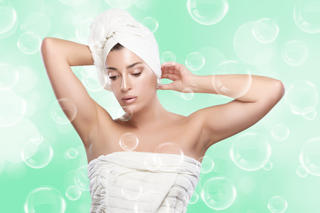 Beautiful young woman in towel after bath. Haircare and bodycare concept. photo