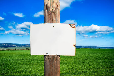 posted: Closeup of rural informative post empty in front of scenic field with space for text
