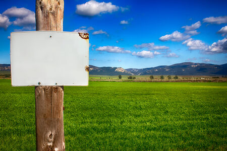 farm sign: Closeup of rural informative post empty in front of scenic field with space for text