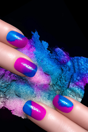 Nail Art. Fingers with luxury nails and crushed eye shadow with drops of water. Manicure and makeup concept. Closeup image isolated on black photo