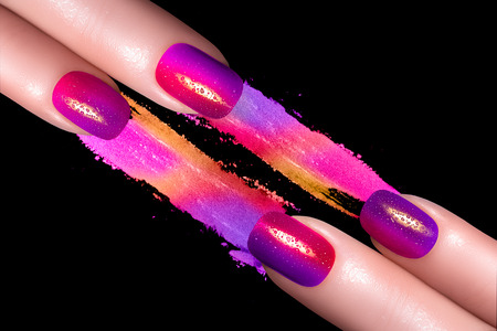 Nail Art. Fashionable fluor nails with drops of water with colorful crushed eyeshadow. Manicure and makeup concept. Closeup image isolated on black