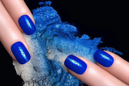 Fashionable blue nails with drops of water and crushed eyeshadow in blue silver. Manicure and makeup concept. Closeup image isolated on black