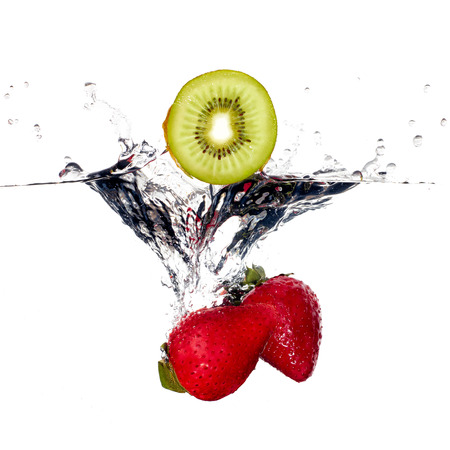 falling water: Strawberries and kiwi falling into clear water isolated on white background. Closeup of fresh and health fruit