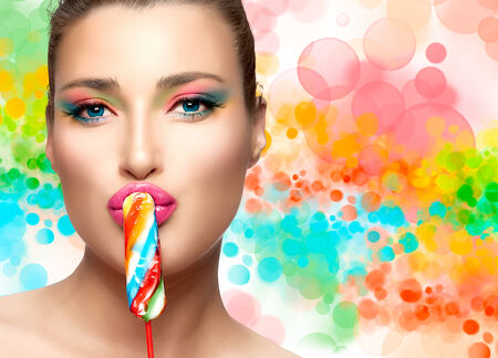 Young beautiful woman with luxury makeup kissing a colorful lollipop looking at camera. photo