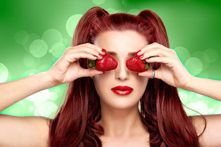 ponytails: Beautiful young woman with ponytails holding strawberries in eyes like binoculars.