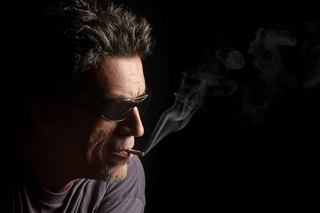 hombre fumando puro: Fumar, hombre de las gafas y un puro en la boca. Primer retrato de media cara sobre fondo negro