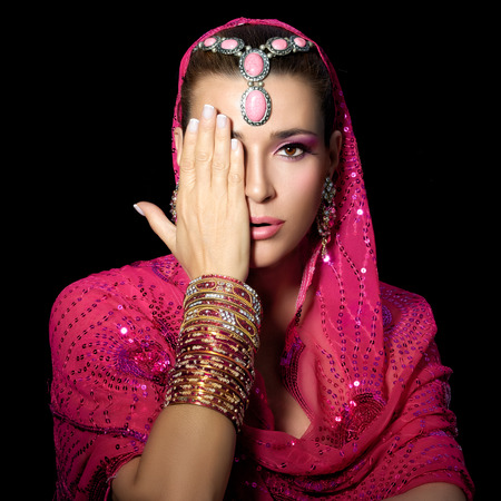 glamour woman: Ethnic beauty. Beautiful hindu woman with traditional clothes, jewelry and makeup covering half face with one hand. Portrait isolated on black