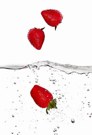 falling water: Closeup of fresh and health strawberrie falling into clear water isolated on white background. Washing the fruit