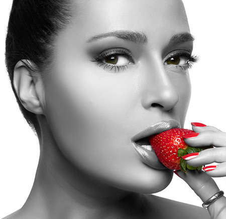 Beautiful young woman eating strawberry. Closeup portrait isolated om white.