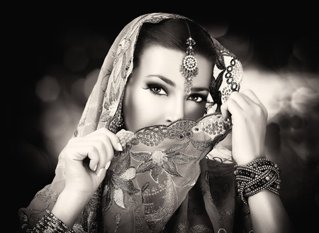 Beautiful hindu woman with traditional clothes, jewelry and makeup. Portrait in black and white