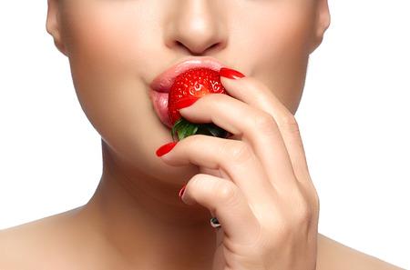 boca sana: Dulce de la mordedura. Hermosa boca sana mordiendo fresa. Close-up retrato aislado en blanco