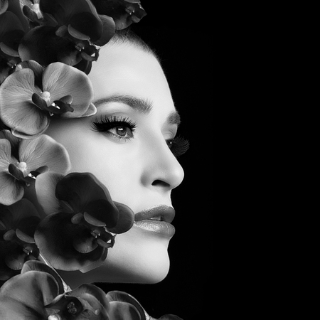 white women: Monochrome portrait of beautiful face woman with flowers. Beauty and makeup concept. Closeup isolated on black background Stock Photo