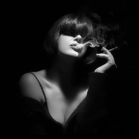 lenceria: Mujer joven que fuma un cigarrillo. Retrato monocromo