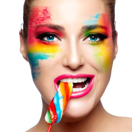 maquillaje de fantasia: Mujer joven hermosa con maquillaje de fantasía de comer una piruleta colorido mirando la cámara. Belleza y el concepto de maquillaje. Retrato del primer aislado en blanco. Foto de archivo