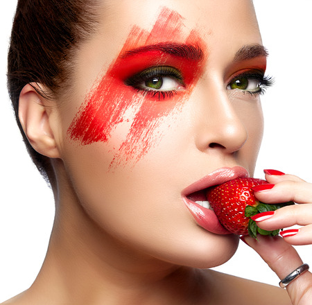 Beautiful young woman with fantasy makeup eating strawberry. Beauty and makeup concept. Closeup portrait isolated on white. photo