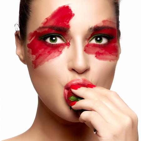 caritas pintadas: Mujer joven hermosa con maquillaje de fantasía de comer fresas. Belleza y el concepto de maquillaje. Retrato del primer aislado en blanco. Foto de archivo