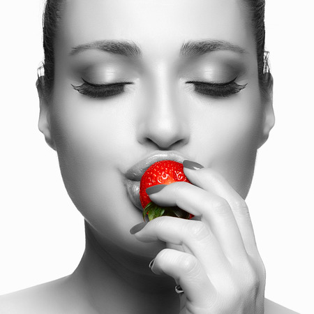 Beautiful young woman eating strawberry. Closeup face portrait isolated on white.