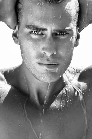Fashionable guy with face wet after swimming. Closeup portrait in black and white. Summer boy