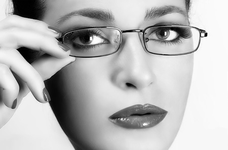 Young woman with glasses. Closeup black and white portrait. Eyecare concept photo