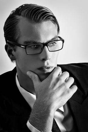 capelli biondi: Riflessivo giovane imprenditore. Uomo bello biondo con gli occhiali guardando all'infinito. Ritratto in bianco e nero Archivio Fotografico
