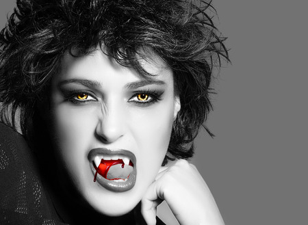 Vampire. Beautiful young woman with fancy makeup, bloody fangs and wolf lenses. Halloween concept. Black and white portrait with copy space