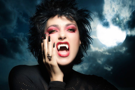 Female werewolf. Beautiful young woman screaming with fangs, wolf lenses and decorated nails. Halloween concept photo
