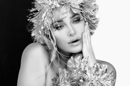 Winter Beauty. Stylish Party Girl with Glamor Silver Hairstyle. Vogue style model with Holiday Silver Makeup and Hairstyle over Black and White Background photo